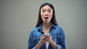 Kvinnaläsningmeddelande på smartphonen och bli extremt lyckligt, lotteriseger lager videofilmer