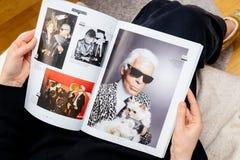 Kvinnaläsningnewsapepr om Karl Lagerfeld död - foto med den Choupette katten royaltyfri bild