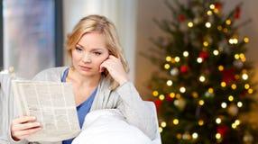 Kvinnaläsningtidning på jul hemma arkivfoton