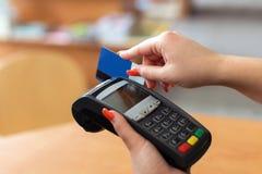 Kvinnalön vid kreditkorten Arkivbild