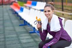 Kvinnalöpare med att vila för handduk och dricksvatten från en flaska, når att ha utarbetat spårkörning av stadion Royaltyfria Bilder