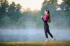 Kvinnalöpare på dimmig morgon nära sjön Arkivbild