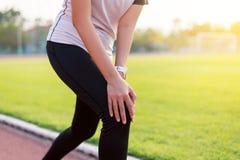 Kvinnalöpare som har ett knä att smärta och skada efter spring, kvinnliga händer som trycker på hennes knä arkivfoton