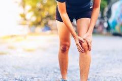 Kvinnalöparehåll hennes sportar sårade knä royaltyfria bilder