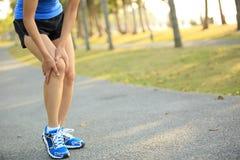 Kvinnalöparehåll hennes sportar sårade knä Royaltyfri Bild