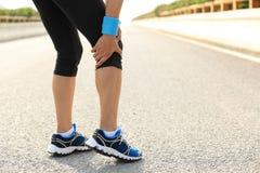 Kvinnalöparen rymmer hennes sårade ben arkivfoto