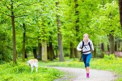 Kvinnalöparen som går med hunden i sommar, parkerar Royaltyfri Foto