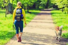 Kvinnalöparen som går med hunden i sommar, parkerar Arkivbilder