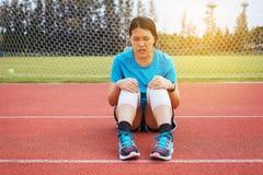 Kvinnalöparen som lidande från smärtar i ben, såras, handen som trycker på hennes knä, når du har joggat på spårspring arkivbilder