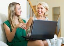Kvinnalearnig som använder bärbara datorn från flicka Arkivbild