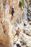 Kvinnaledningsklättring på den naturliga klippan, grabbbelayer som håller ögonen på henne fotografering för bildbyråer