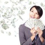 Kvinnaleende som är lyckligt med handfullpengar arkivfoto