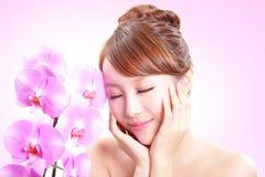 Kvinnaleendeframsida med orkidéblommor Fotografering för Bildbyråer