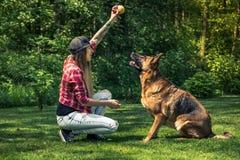 Kvinnalek med hennes hund i trädgård på sommar Royaltyfri Fotografi