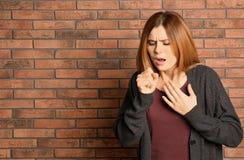 Kvinnalidande från hosta nära tegelstenväggen royaltyfri fotografi