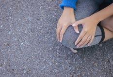 Kvinnalidande från smärtar i ben eller knäskada efter att ha joggat och genomkörare för sportövningsspring royaltyfri fotografi
