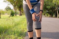 Kvinnalidande från smärtar i ben och knäskada, efter körande jogga med genomkörare har parkerat offentligt arkivbild