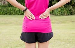Kvinnalidande från smärtar i tillbaka skada efter att ha joggat och genomkörare för sportövningsspring royaltyfri bild
