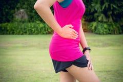 Kvinnalidande har magen att smärta, kvinnliga löparesidokramper efter sportövningsspring royaltyfria foton