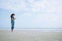 Kvinnalivsstil genom att använda en Smartphone på stranden Arkivfoto