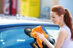 Kvinnalokalvård som är torr torka hennes svarta bil på solig dag för sommar royaltyfri foto