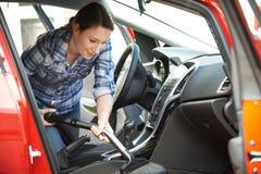 Kvinnalokalvårdinre av bilen genom att använda dammsugare Arkivfoton