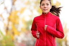 Kvinnalöpare som kör i höst Arkivfoto