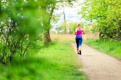 Kvinnalöparespring som joggar i sommar, parkerar Arkivbilder
