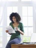 Kvinnaläsningdokument hemma Arkivbilder
