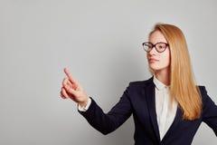 Kvinnalyftande finger förestående till pekskärmen arkivbild