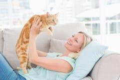 Kvinnalyftande katt på soffan hemma Arkivbild
