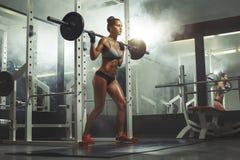 Kvinnalyftande skivstång med vikt i idrottshall fotografering för bildbyråer