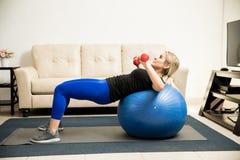 Kvinnalyftande vikter och använda stabilitetsbollen Arkivbild