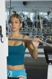 Kvinnalyftande vikter på en Lathandtagmaskin Royaltyfri Bild