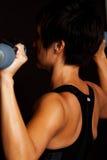 Kvinnalyftande vikter som isoleras på svart Arkivfoto