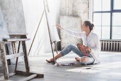 Kvinnamålare på workspace royaltyfri foto