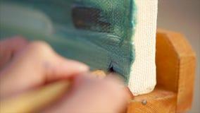 Kvinnamålare som undertecknar hennes konstarbete lager videofilmer