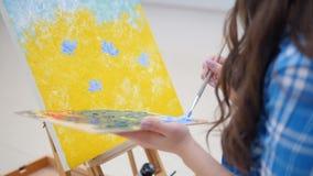 Kvinnamålaremålning med olje- målarfärger på en vitbok lager videofilmer