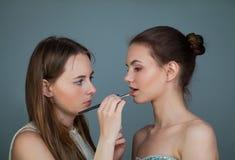 Kvinnamakeupkonstnär som rymmer makeupborstar och applicerar läppstift på den perfekta kanten för modemodell arkivfoto