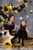 Kvinnamaktpartiet med den härliga modellmodern och gulligt behandla som ett barn iklädda luftiga svarta maskeradkläder för dotter arkivfoto