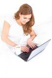 Kvinnamaskinskrivning på bärbar datordatoren hemma i morgonen Arkivbilder