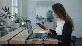 Kvinnamaskinskrivningen och le vid bärbara datorn arkivfilmer