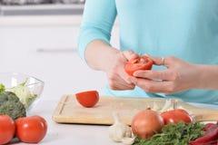 Kvinnamatlagning i nytt kök som gör sund mat med grönsaker Arkivfoto