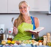 Kvinnamatlagninggrönsaker med nytt recept Arkivfoto