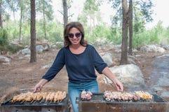 Kvinnamatlagningkött på bärbar grillfest Arkivfoto
