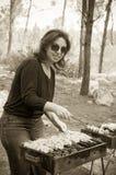 Kvinnamatlagningkött på bärbar grillfest/sepia Royaltyfria Foton