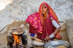 Kvinnamatlagningmat på wood brand royaltyfri bild