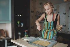 Kvinnamatlagningpizza på kök Royaltyfria Foton