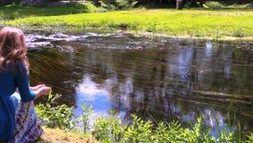 Kvinnamatning med fåglar för den lösa anden för bröd simmar i den flödande floden Arkivbilder