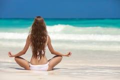 Kvinnameditation på den tropiska stranden Royaltyfri Bild